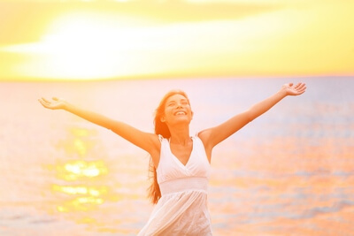 Freedom woman happy and free open arms on beach at sunny sunset. Beautiful joyful elated woman looking up smiling by the ocean during summer holidays vacation. Pretty multiracial Asian Caucasian girl.